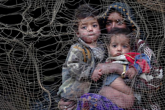 أم أفغانية وطفليها ينظرون من خلال مسكنهم المهدم