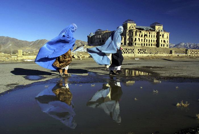 امرأتان أفغانيتان أمام قصر قندهار في كابول في يوم ممطر