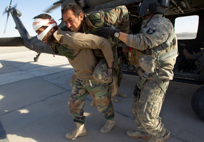 جندي أفغاني يحمل زميله المصاب جراء قصف للطائرات الأمريكية في كابول