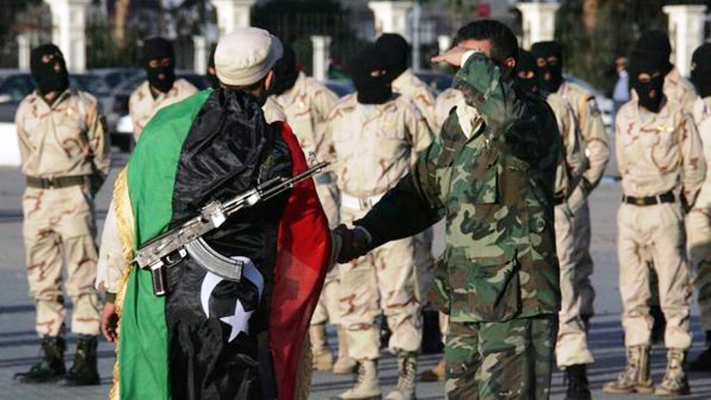 A Libyan officer shakes hands with a former member of the anti-Kadhafi rebel movement who joined the National Army's commando force during a military parade in the Mediterranean port of Benghazi in eastern Libya on February 23, 2012. Libya's army chief said troops were preparing to enter the southeastern desert city of Kufra, to secure the area that has been at the heart of deadly ethnic clashes.    AFP PHOTO/STR (Photo credit should read STR/AFP/Getty Images)