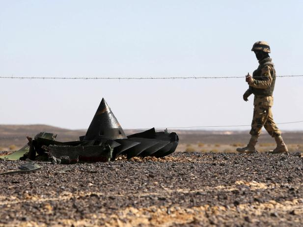 أحد جنود الجيش المصري، يقوم بالحراسة بالقرب من حطام الطائرة الروسية، التي تحطمت في منطقة الحسنة في مدينة العريش شمال مصر. (الصورة لمحمد عبد الغني/رويترز).