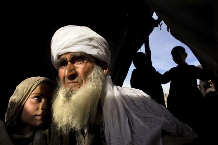 شيخ أفغاني يحتضن حفيدته في أحد المخيمات بعد أن قُصِفت قريتهم