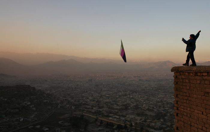 طفل أفغاني يحرك طائرة ورقية ساعة شروق الشمس على العاصمة كابول