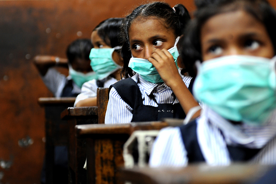 Indian school children, wearing protective masks distributed by the local right wing Shiv Sena party for an awareness campaign, are seen in a classroom in Mumbai on August 10, 2009. The number of people to die from swine flu in India rose to six, health officials said, as the government called for calm and people flocked to public hospitals for tests. The latest to die of the (A)H1N1 virus were an ayurvedic or traditional medicine practitioner in Pune, 120 kilometres (75 miles) from India's financial hub Mumbai, and a four-year-old boy in the southern city of Chennai.      TOPSHOTS/AFP PHOTO/ Pal PILLAI (Photo credit should read PAL PILLAI/AFP/Getty Images)