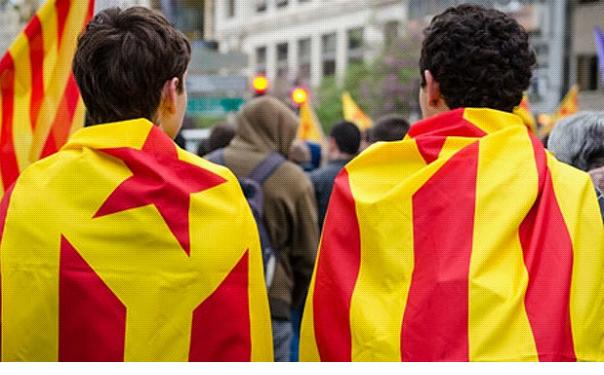 انفصاليان يتوشحان بأعلام كتالونيا في مظاهرات العام الماضي