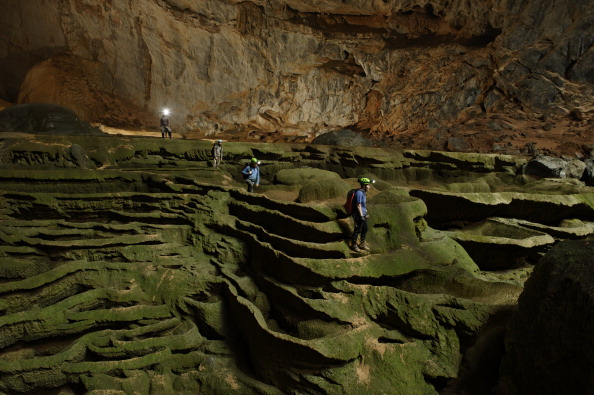 Hang Son Doong explorers navigate an algae-covered cavescape.