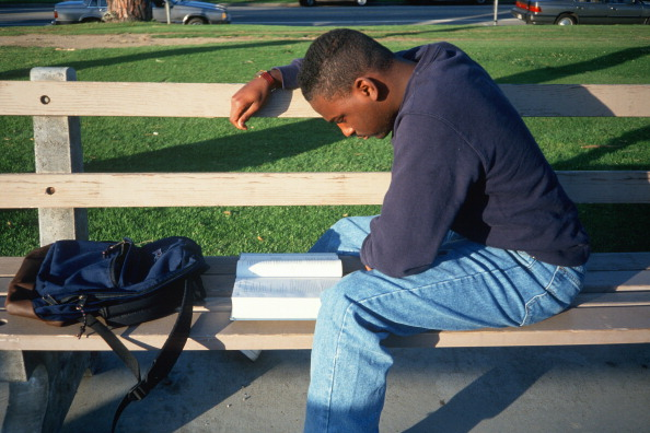 Male African American student studying on a bench, Santa Monica, California