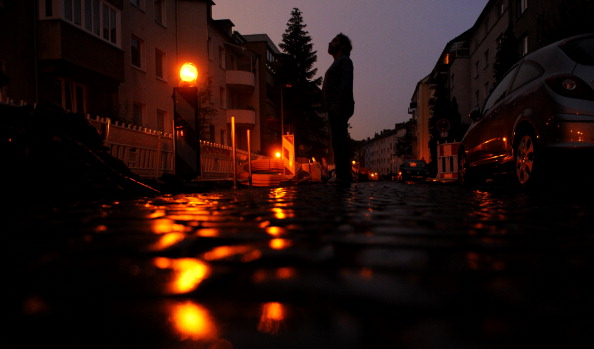 A man stands in a dark street in Hanover