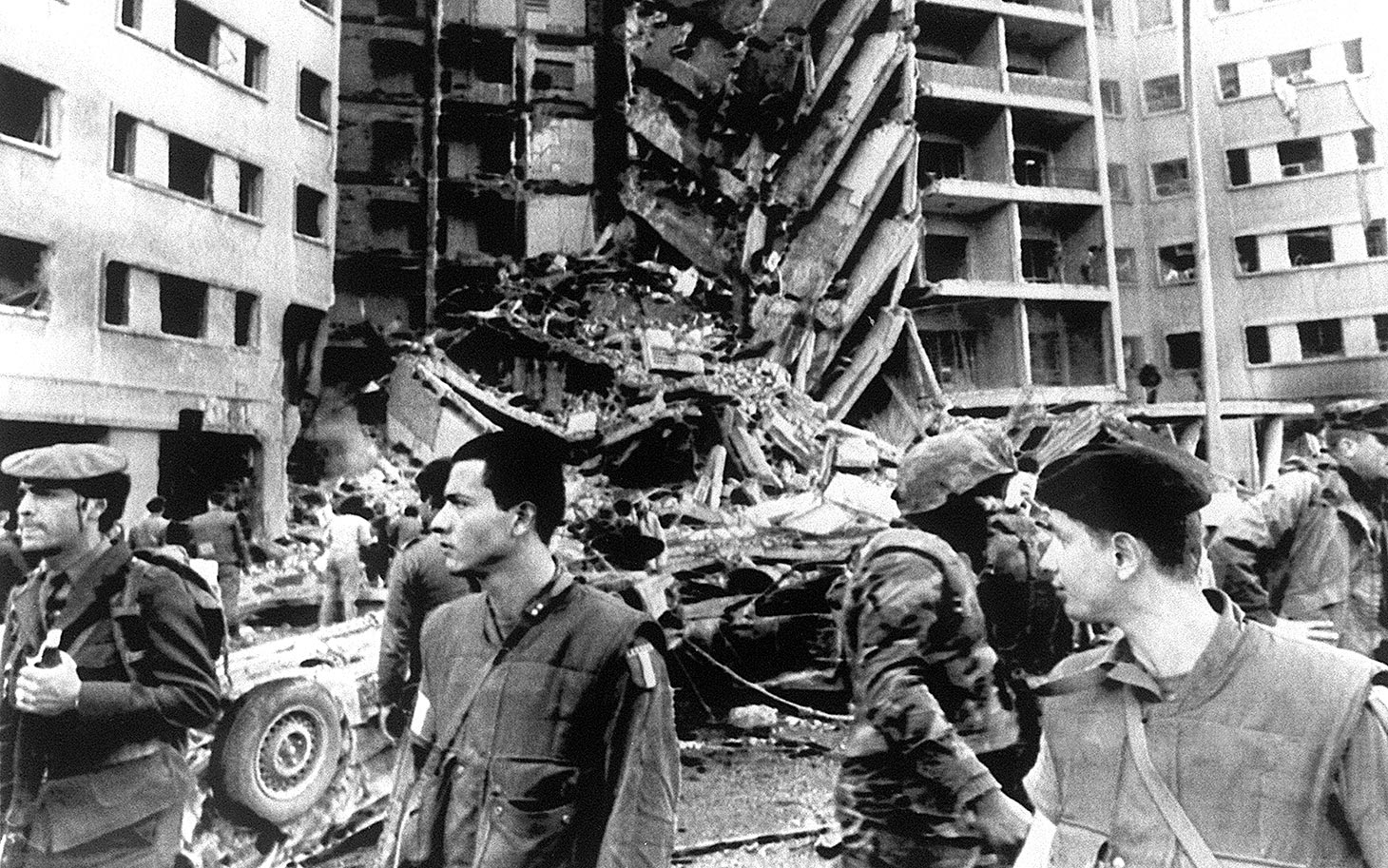 A Lebanese policeman (far L), a French soldier, a U.S. Marine (with helmet) and a French soldier stand guard 18 April 1983 in front of the destroyed section of the U.S. embassy in Beirut. A bomb partially destroyed the building killing and injuring scores of people. (Photo credit should read -/AFP/Getty Images)