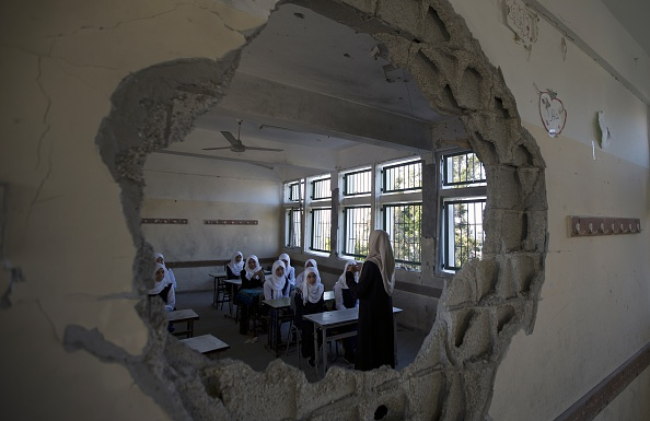 Palestinian students are seen through a damaged sitting in a classroom at a goverment school in the Shejaiya neighbourhood of Gaza City on September 14, 2014 on the first day of the new school year. Half a million children in Gaza start the new school year three weeks late as a result of the devastating 50-day war between Israel and Hamas that ended on August 26, 2014. AFP PHOTO/MAHMUD HAMS (Photo credit should read MAHMUD HAMS/AFP/Getty Images)