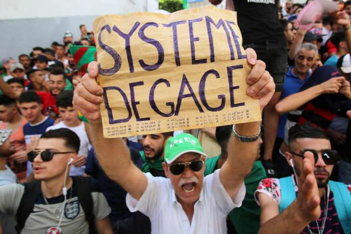 متظاهرون غاضبون يرفعون لافتة النظام إرحل