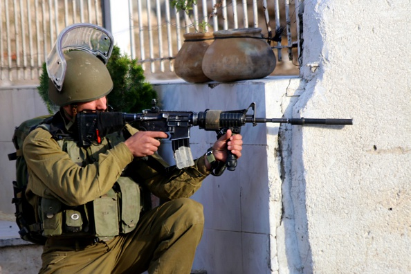 An Israeli soldier aims his M-16 at Palestinian youth