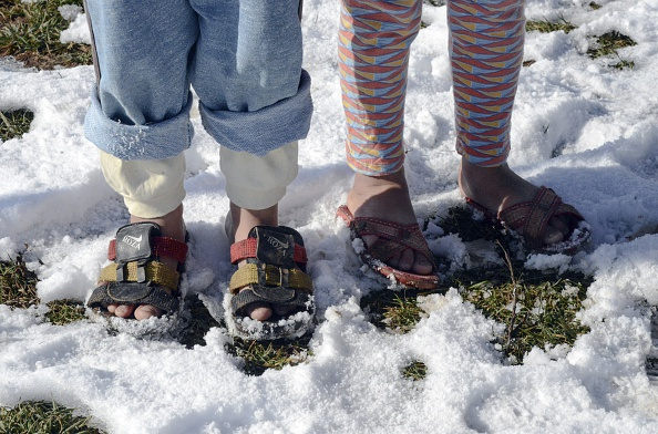 Yazidi children refugees wearing sandals, pose at a refugee camp after a snowfall in the main Kurdish-majority city of Diyarbakir in southeastern Turkey, on January 10, 2015. AFP PHOTO/ILYAS AKENGIN (Photo credit should read ILYAS AKENGIN/AFP/Getty Images)