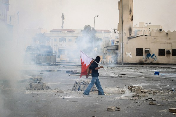 MANAMA, BAHRAIN - 2015/02/13: Demonstrator peacefully carries the flag of Bahrain in one of the streets that are filled with toxic gas used by the Bahraini forces during the clashes, which came one day before the fourth anniversary of the Bahraini uprising, called revolution February 14, in Sitra south of the capital Manama. (Photo by Ali Hussain/Pacific Press/LightRocket via Getty Images)