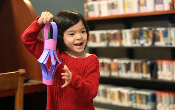 WAKEFIELD, MA - FEBRUARY 20: Bella Guo 4, of Reading, Mass., shows her mom a paper lantern she just made. It was a craft project to celebrate the Chinese New Year at Wakefield's Lucius Beebe Memorial Library. (Photo by Joanne Rathe/The Boston Globe via Getty Images)