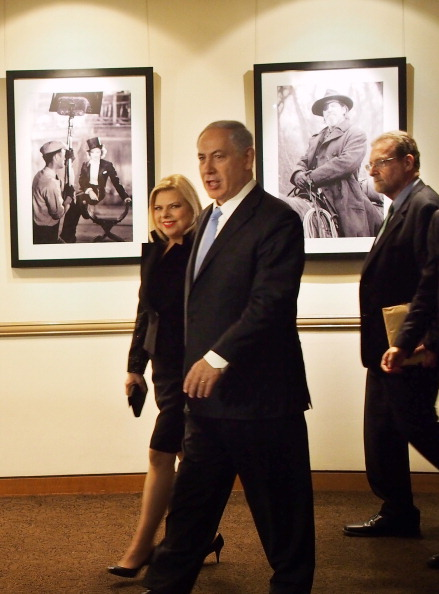 """Israeli Prime Minister Benjamin Netanyahu, accompanied by his wife Sara Netanyahu, walks past still photos from famous Paramount movies as he arrives for a reception at Paramount Studios in Los Angeles, California, March 4, 2014.  Netanyahu attending a screening of """"Israel: The Royal Tour'' --  a television documentary in which Netanyahu is featured.  The Israeli prime minister flew Tuesday from Washington, D.C., to California for a two-day visit.   AFP PHOTO / ROBYN BECK        (Photo credit should read ROBYN BECK/AFP/Getty Images)"""