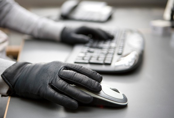 GERMANY, BONN - JUNE 26: Cybercrime. Hands with black gloves on computer keyboard and mouse. (Photo by Ulrich Baumgarrten via Getty Images)