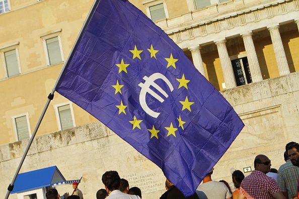 A protester waves a large European flag with a Euro sign in