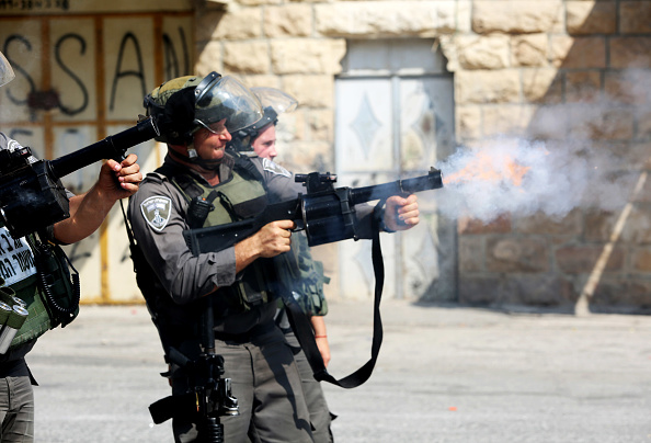 Israeli soldiers fire tear gas into Palestinian