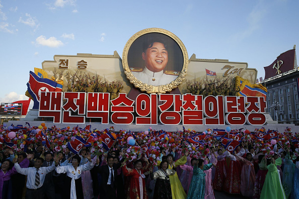 PYONGYANG, NORTH KOREA - OCTOBER 10: (CHINA OUT) Participants wave flowers during a mass military parade with a portrait of North Korean leader Kim Jong Un at Kim Il-Sung square to mark the 70th anniversary of its ruling Worker's Party of Korea on October 10, 2015 in Pyongyang, North Korea. (Photo by Liu Xingzhe/ChinaFotoPress via Getty Images)