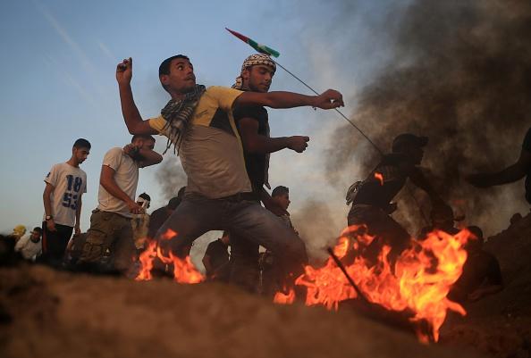محتجون فلسطينيون يقذفون الجنود الإسرائيليين بالحجارة، في قطاع غزة. 13 أكتوبر 2015