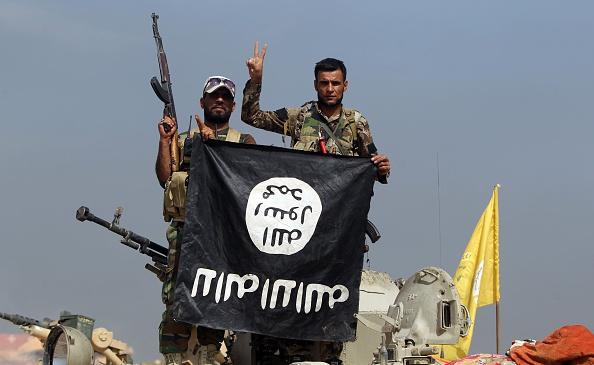 """مقاتلين من """"الحشد الشعبي"""" يحملون علم داعش مقلوبًا، شمالي بغداد. 19 أكتوبر 2015"""