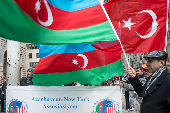 Attendees of the event hold Azerbijani and Turkish flags.