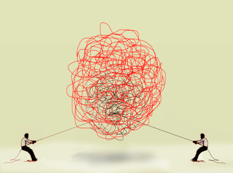 Two men pulling at tangled rope in opposite directions