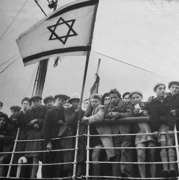 Jewish immigrants, arriving in Haifa aboard a refugee ship, waving future flag of the state of Israel shortly before its official conception.  (Photo by Dmitri Kessel/The LIFE Picture Collection/Getty Images)