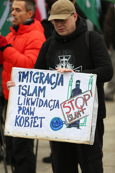 """A man hold a poster that reads, """"Immigrants of Islam will"""