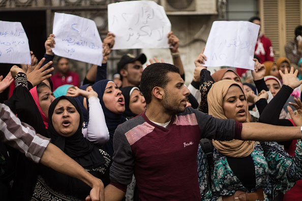 Students raising poster during demonstration in Egypt.