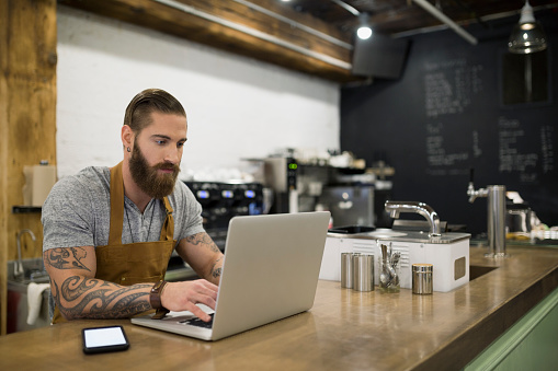 Hipster barista working at laptop in coffee shop
