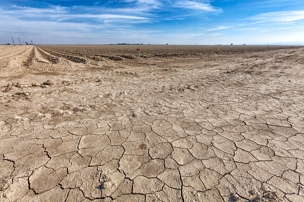 Cracked and dry earth next to fallow crop field. Fresno County, San Joachin Valley, California. (Photo by: Citizens of the Planet/Education Images/UIG via Getty Images)