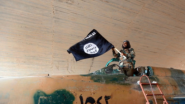 Islamic State fighter (ISIS; ISIL) waving a flag while standing on captured government fighter jet in Raqqa, Syria, 2015. (Photo by: Universal History Archive/UIG via Getty Images)
