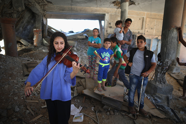 GAZA CITY, GAZA - JUNE 13: During a music workshop for traumatised children, Tamara Abu Ramadan a volunteer with the Tamer Institute plays ger violin in a bombed mosque. Using music, art, crafts and companionship as part of the process to help them overcome the mental trauma of war. Tamer volunteers organised a musical workshop for local children amongst the rubble and bomb sites of Gaza City on June 13, 2015, Gaza City, Gaza. The devastation across Gaza can still be seen nearly one year on from the 2014 conflict between Israel and Palestinian militants. Money pledged by the international community six months ago to rebuild Gaza has not materialised leaving many Palestinians impoverished and still suffering with the poor economy. United Nations official figures said that the 50 day war left at least 2,189 Palestinians dead, including more than 1,486 civilians, and 11,000 injured. 67 Israeli soldiers and six civilians were killed. (Photo by Christopher Furlong/Getty Images)
