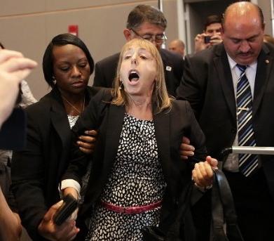 بينجامين أثناء انفعالها على أوباما بينما يسعى الآخرون لتهدئتها