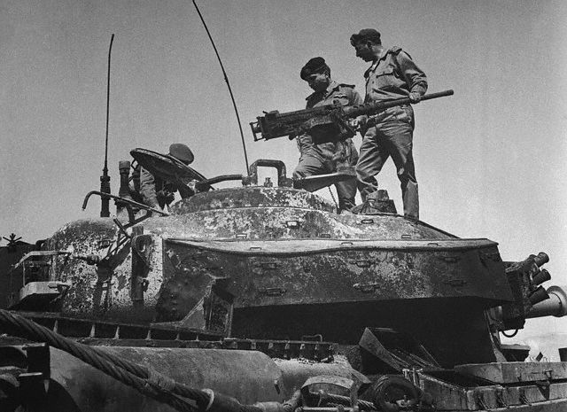 22 Mar 1968, Amman, Jordan --- King Inspects Tank.  Amman, Jordan:  Jordan's King Hussein (wearing dark beret) stands on a tank which, according to Jordanian sources, was left behind by Israeli forces at the frontier following the March 21st attack.  The Jordanian military command said 45 Israeli tanks were destroyed and five fighter planes shot down before the Israelis withdrew across the Jordan River after the attack against Arab saboteur bases. --- Image by © Bettmann/CORBIS