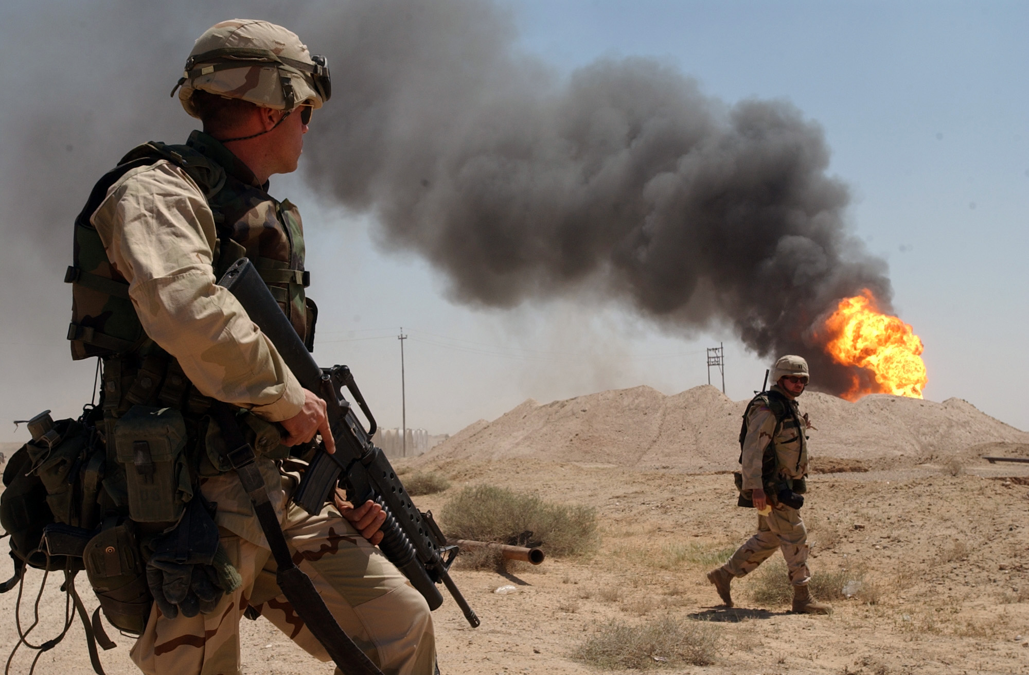 030402-N-5362A-004 Southern, Iraq (Apr. 2, 2003) -- U.S. Army Sgt. Mark Phiffer stands guard duty near a burning oil well in the Rumaylah Oil Fields in Southern Iraq.  Coalition forces have successfully secured the southern oil fields for the economic future of the Iraqi people and are in the process of extinguishing the burning wells that were set ablaze in the early stages of Operation Iraqi Freedom.  Operation Iraqi Freedom is the multi-national coalition effort to liberate the Iraqi people, eliminate Iraq's weapons of mass destruction and end the regime of Saddam Hussein.  U.S. Navy photo by Photographer's Mate 1st Class Arlo K. Abrahamson.  (RELEASED)
