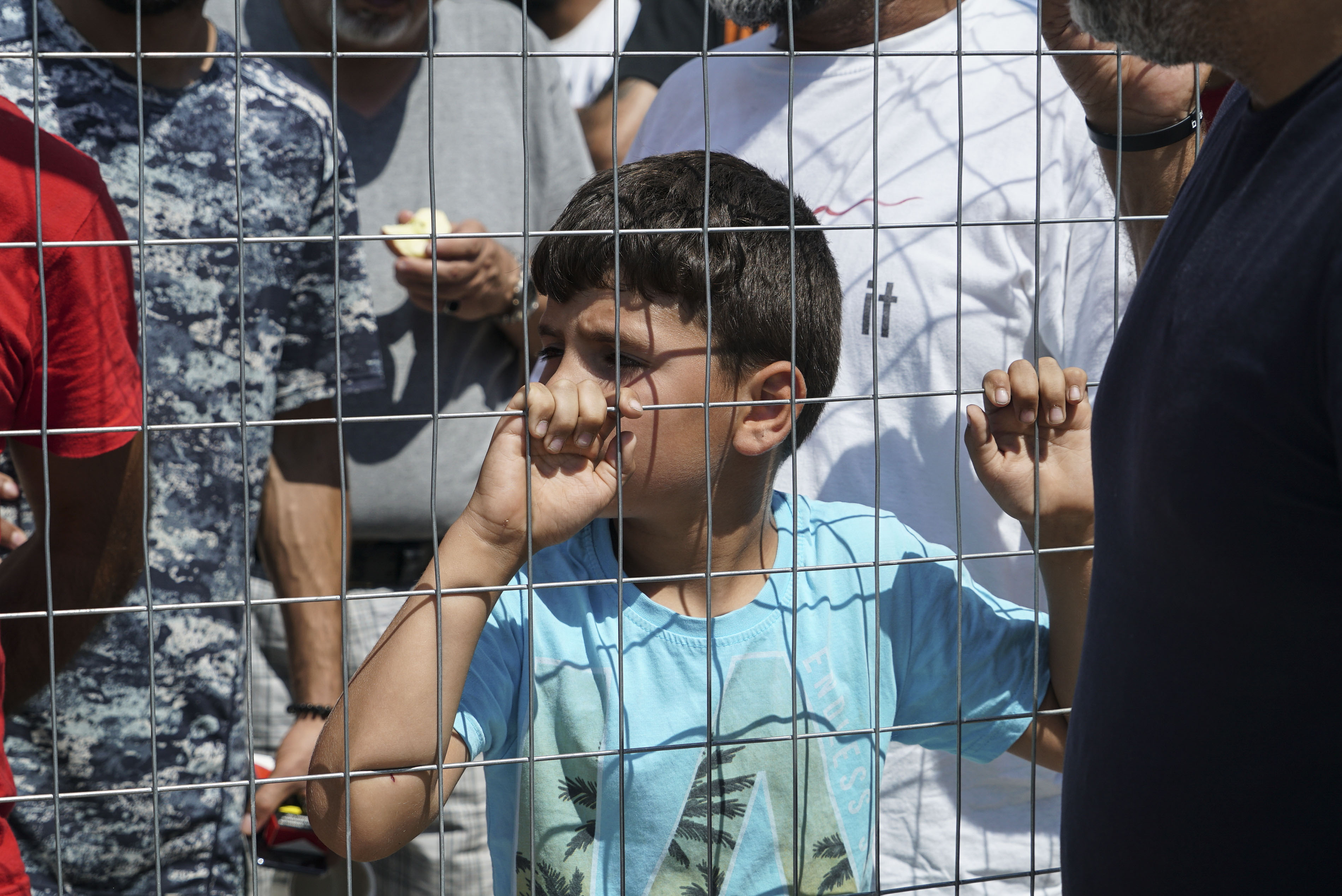 طفل من اللاجئين السوريين وراء سياج مخيم في اليونان أوروبا اللاجئين كورونا